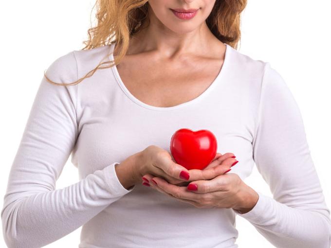 胸の前でハートを持っている女性の画像