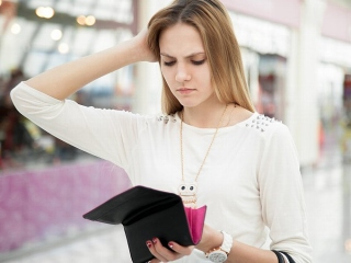 財布の中身を見て頭を抱える女性