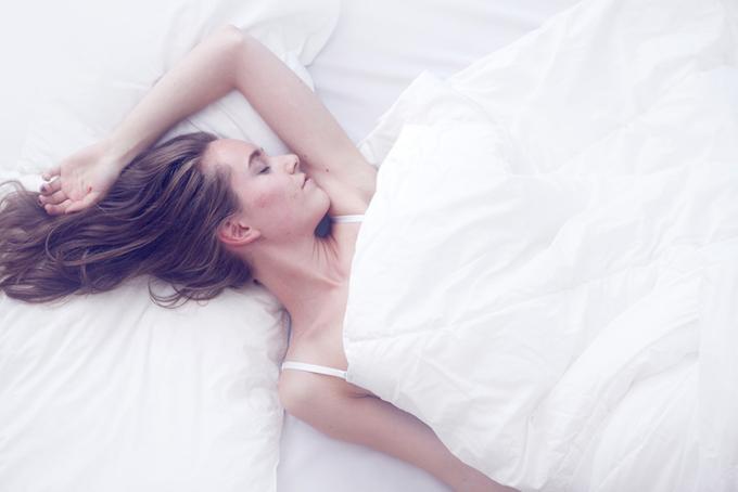 ベッドの上で女性が横になって寝ている画像