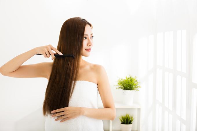 ロングヘアの女性が髪の毛をとかしている