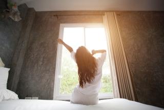 ベッドから起き上がった女性の画像