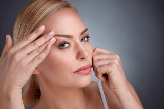 目元の皮膚を伸ばしている女性の画像