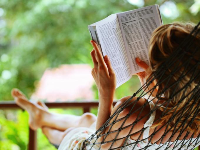 ハンモックの上で読書をする女性の画像