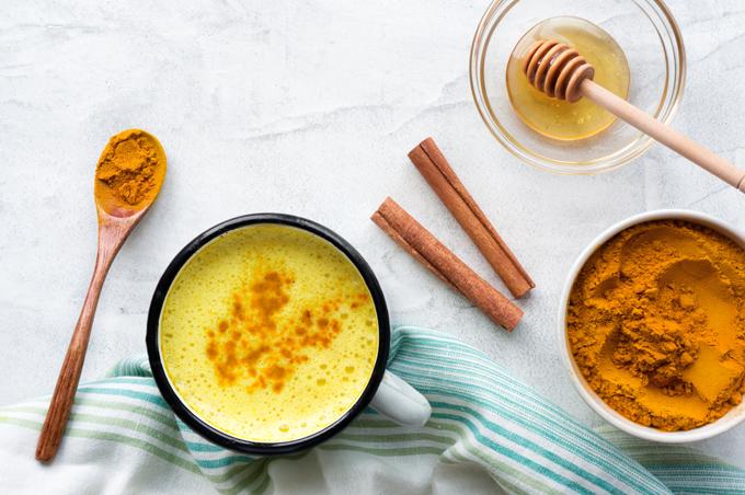 カップの中にウコンのドリンク、右にシナモンや蜂蜜が置いてある画像