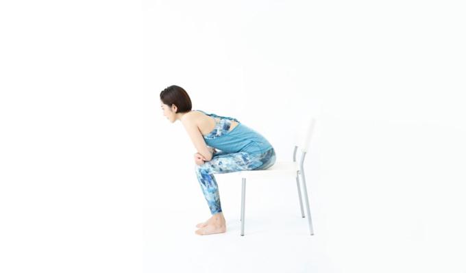 椅子に座り、前かがみになっている様子