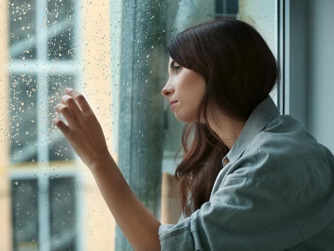 窓辺で雨を見る女性の画像