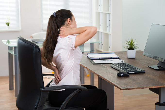 机に座って腰と首を押さえている女性の画像