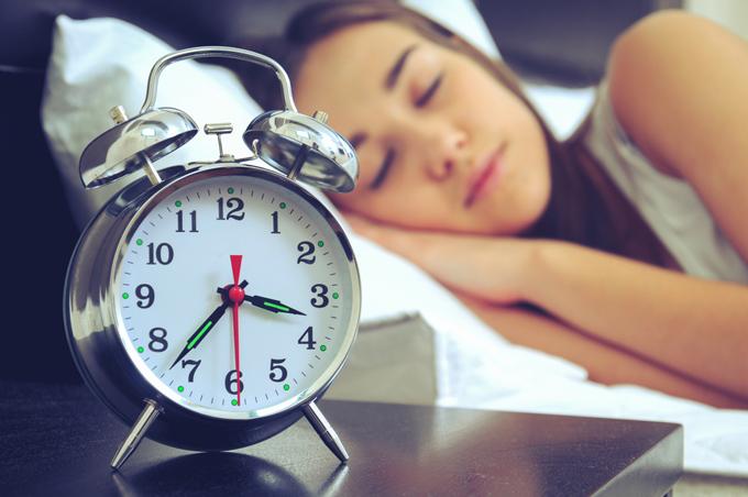 ベッドで寝ている女性と目覚まし時計の画像