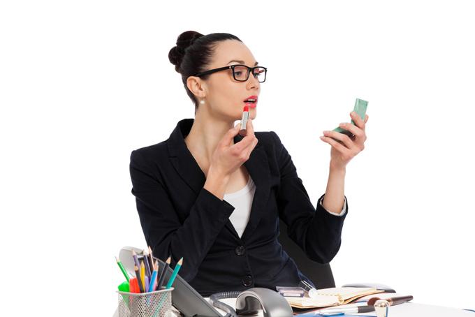 デスクで口紅を塗っている眼鏡をかけた女性の画像