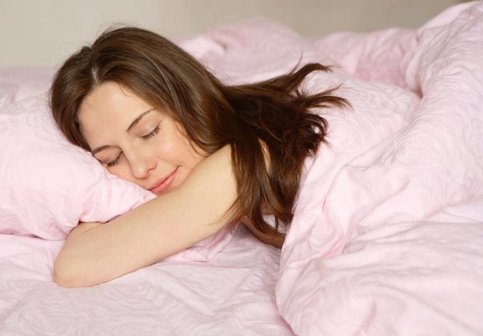 ピンクの寝具で女性が寝ている画像