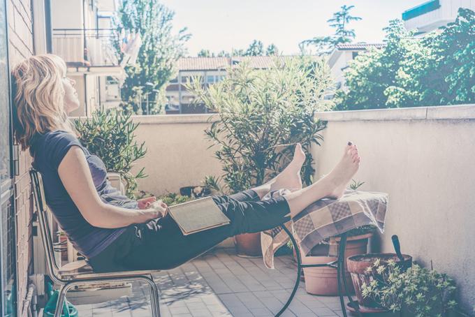 ベランダで日差しを浴びてくつろいでいる女性