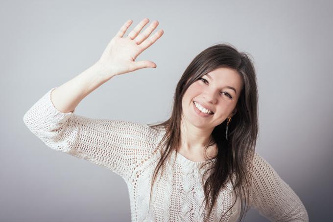 手を左右に振る女性の画像