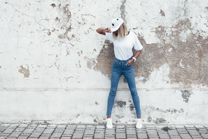 デニムを履いて壁際に立っている帽子をかぶった女性の画像