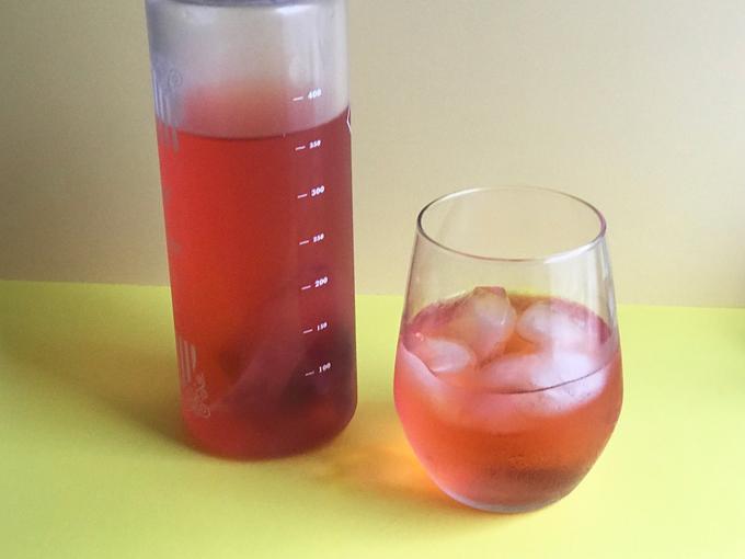 水出ししてボトルとコップに入った赤いざくろ&ローズヒップティ