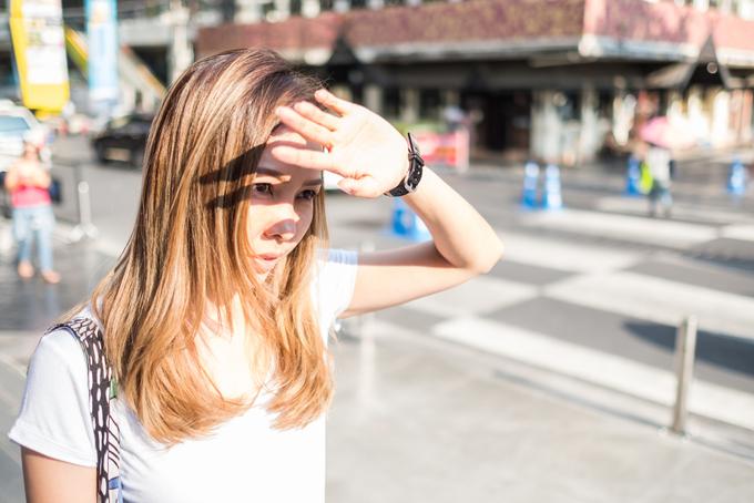 日差しを手で遮る女性の画像