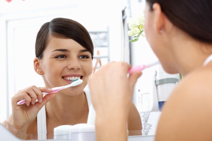 鏡に向かって歯磨きをしている女性の画像