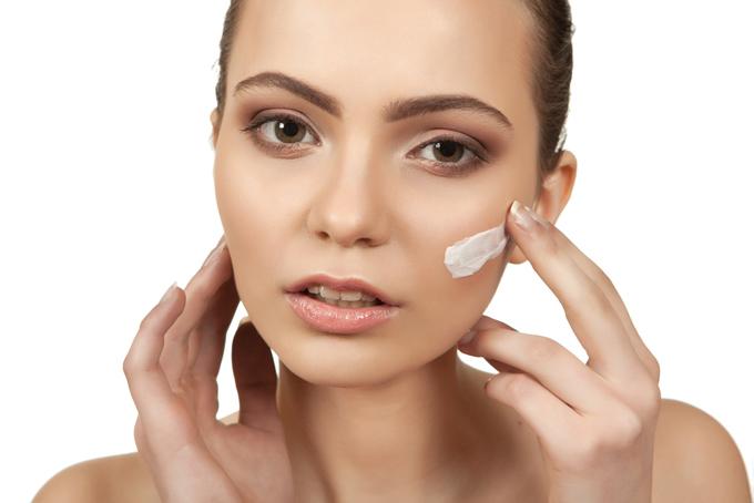 頬にクリームを塗っている女性の画像