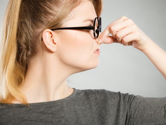 鼻をつまむ女性の写真
