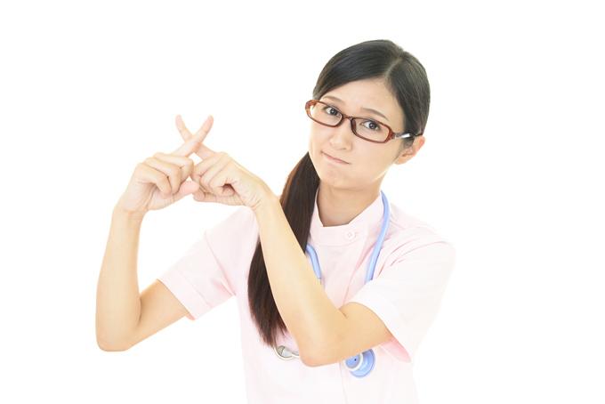 指をバツの形にする女性の画像