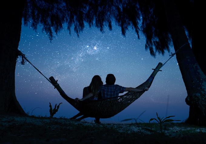 ハンモックに座った男女が星空を眺めている画像