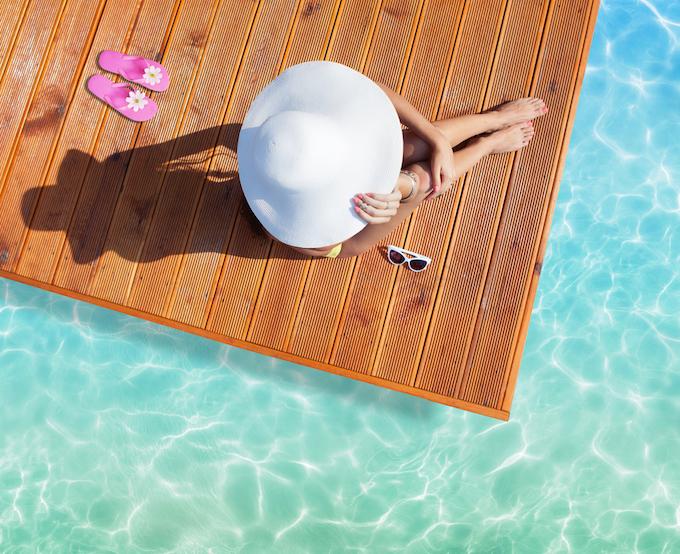 きれいな海辺で白い帽子をかぶった女性