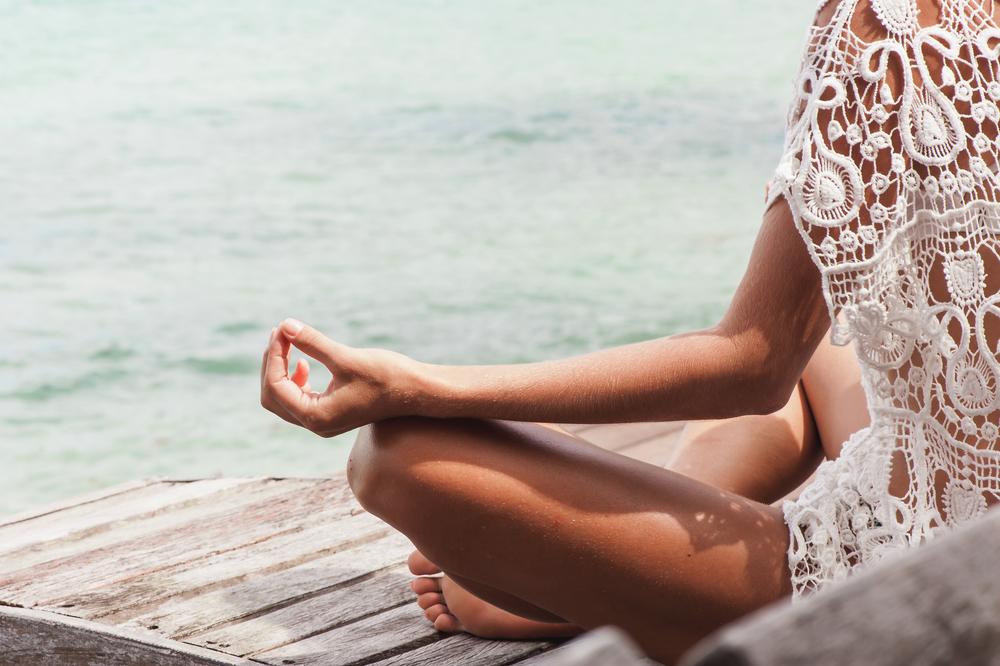 水辺で瞑想している女性の後ろ姿