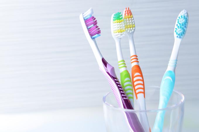 コップに立てかけられている4本の歯ブラシの画像
