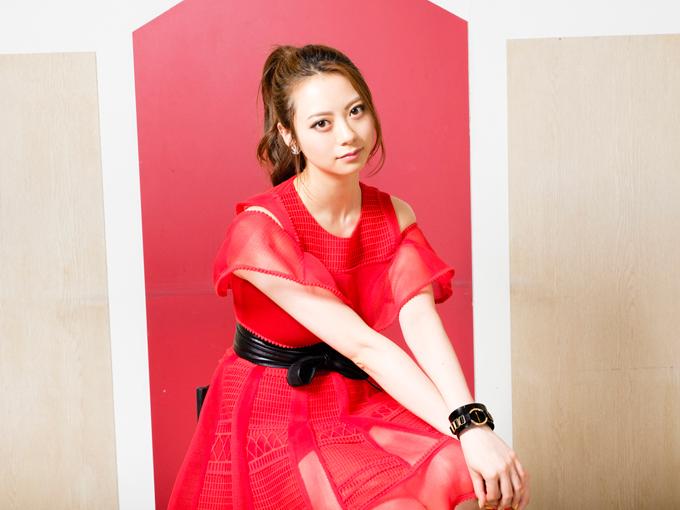 赤い衣装でイスに座る山下リオさん
