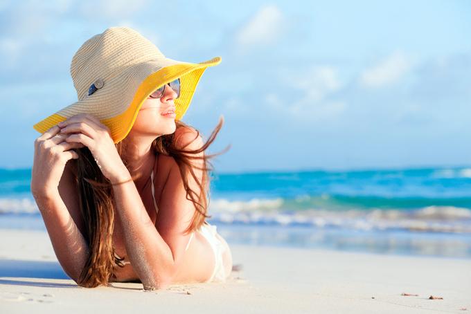 海を眺めて黄昏ている帽子を被った女性