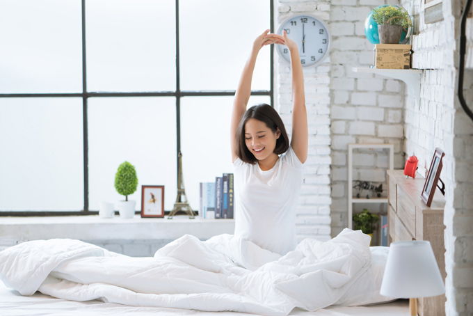ベッドの上で伸びをしている女性の画像