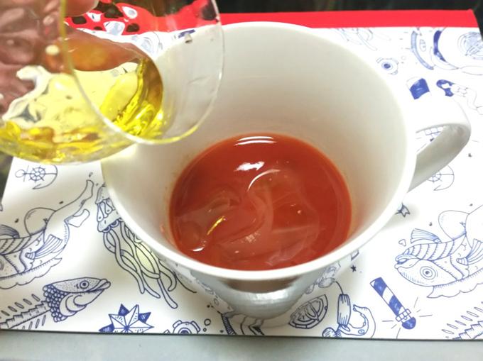 トマトジュースにオリーブオイルを入れている所