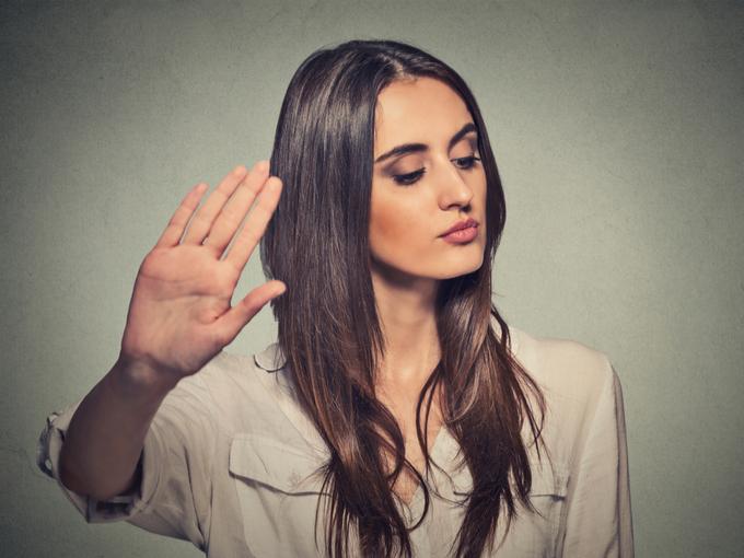 拒否するしぐさを見せる女性
