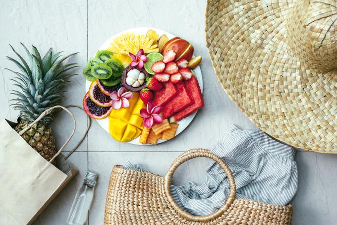 夏っぽい帽子やバック、お皿に盛ったフルーツ