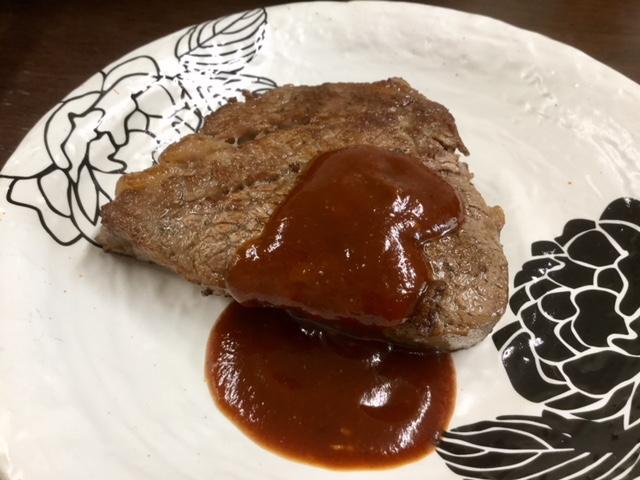 お皿に移してソースをかけたステーキ