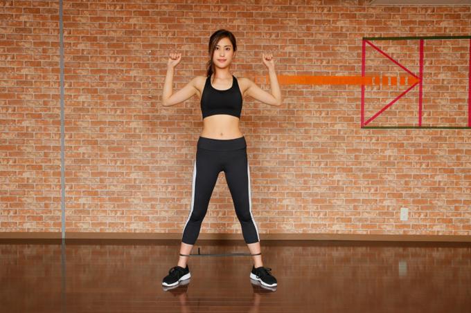足にチューブをひっかけてトレーニングする女性