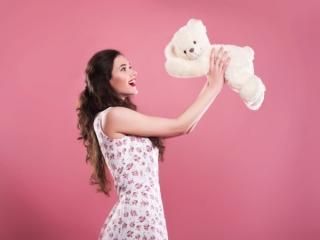クマのぬいぐるみを持ち上げている女性の画像