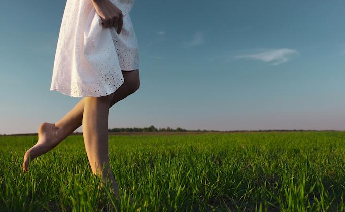 草の上で女性が歩いている画像