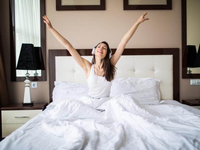 ヘッドホンをつけて起床した女性の画像