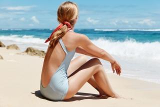 砂浜に座る水着姿の女性