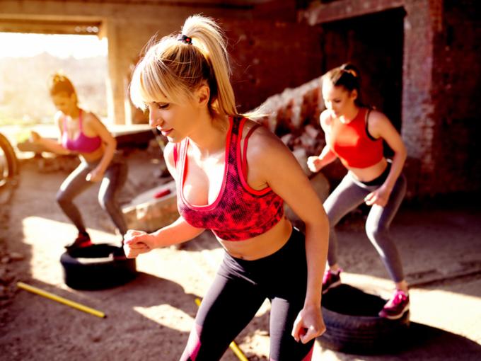 タイヤの上でトレーニングする女性たち