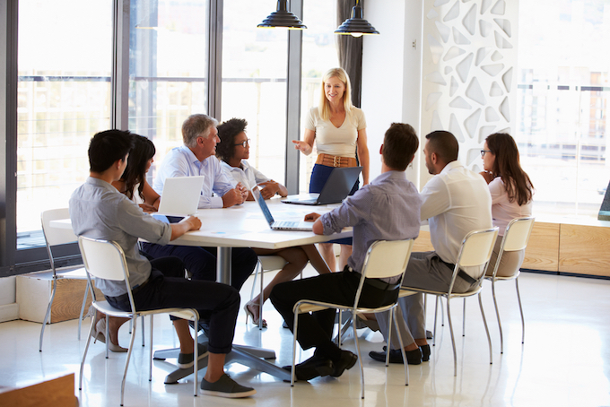 会議中に女性が立って話をしている画像