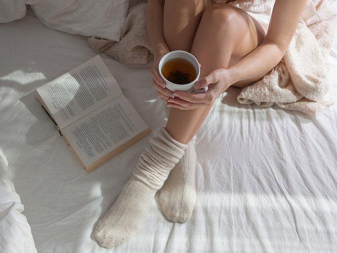 ベッドの上で本を開き、温かい飲みものを飲む女性