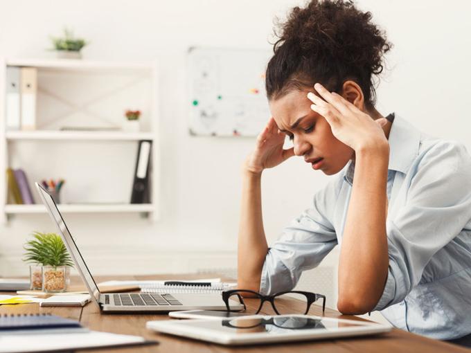 デスクで頭を押さえている女性の画像