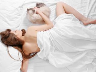 ベッドで猫と眠る女性