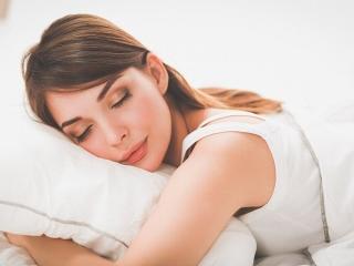 ベッドで眠りにつく女性