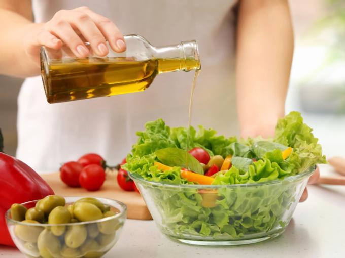 野菜にオイルをかける女性の手元