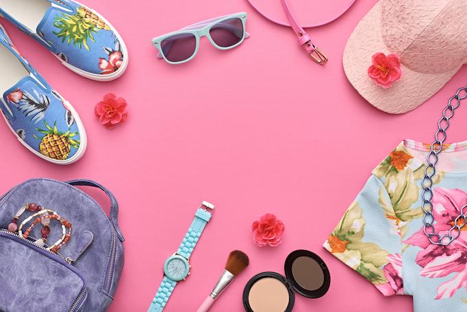 ピンク色の背景にファッションアイテムが並んでいる画像