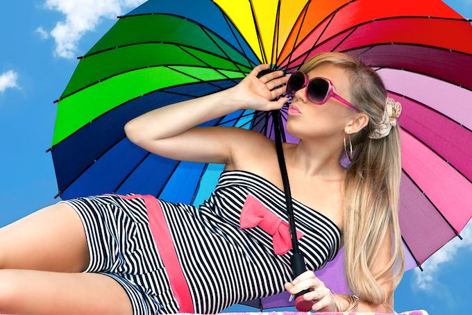 サングラスをかけた女性が日傘を差している画像