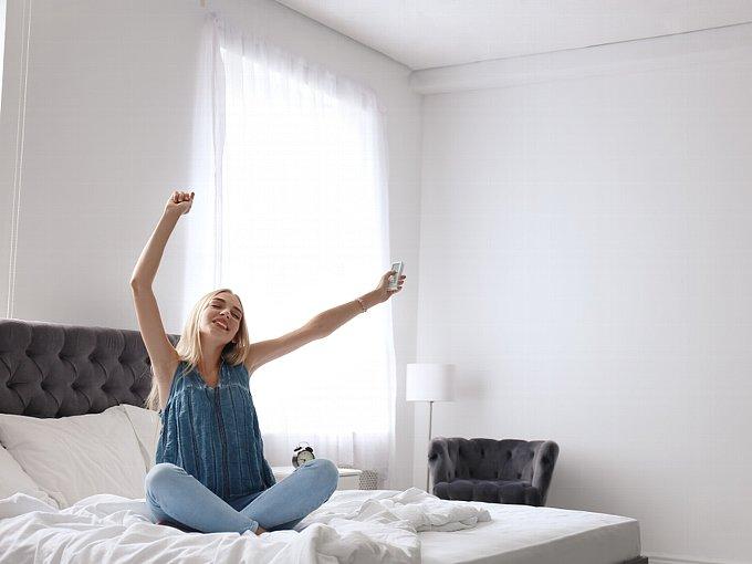 ベッドの上でエアコンのリモコンを手に、伸びをする女性