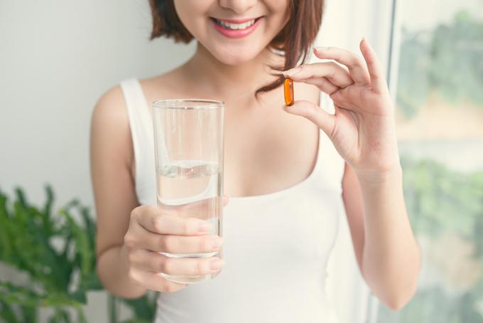 サプリメントと水を持っている女性